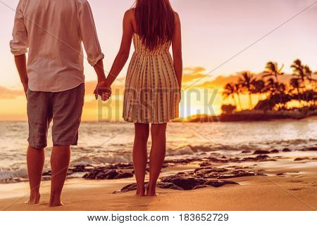Beach couple watching sunset holding hands. People from behind relaxing enjoying summer travel vacation on tropical destination.
