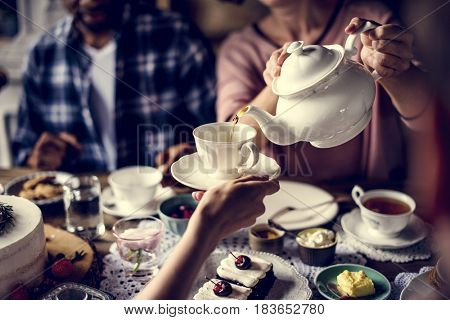 People celebrate birthday party with cake and tea