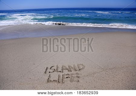 words Island Life written in sand on the beach with the ocean tide and waves