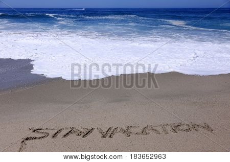 words Vacation and Staycation or Stay Vacation written in sand on the beach with ocean tide and waves