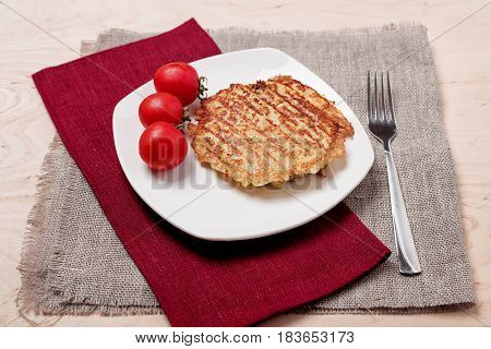 Chop the small red tomatoes on a plate and sackcloth rustic style