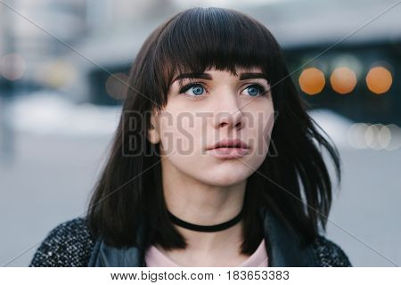 portrait of a young beautiful brunette girl with blue eyes large and interested look