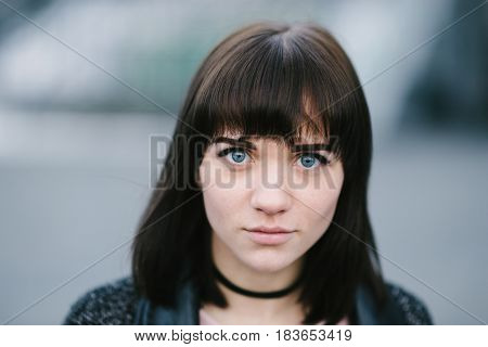street portrait of young beautiful brunette girl with blue eyes and big soulful eyes