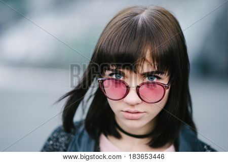 outdoor portrait of a young and very beautiful brunette with big blue eyes in a pink glasses
