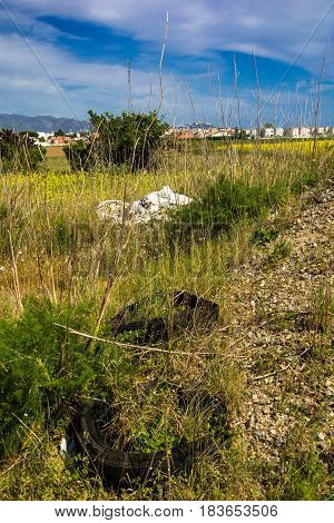 Discarded old tyres and plastic bags grassy wasteland