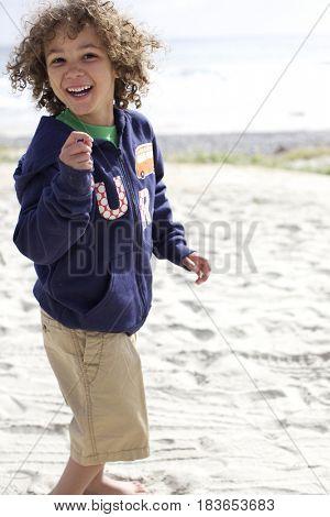 Mixed race boy playing on beach