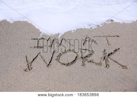 words Im at work written in sand on the beach with the ocean tide and sea waves