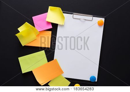 School stationery - many colorful sticky blank notes on black board and empty note paper, top view. Mockup for check-list
