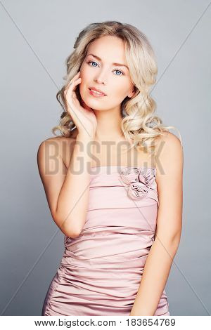Pretty Blonde Fashion Model Woman with Blonde Curly Hair and Makeup. Nice Girl Wearing Pink Silky Dress