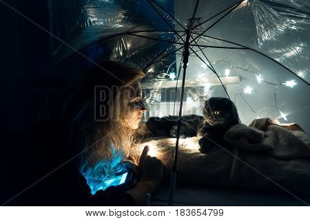 A cat and a young woman under an umbrella with garlands in a room on the bed