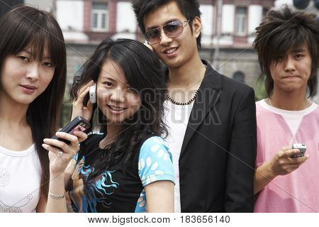 Chinese friends text messaging and talking on cell phones
