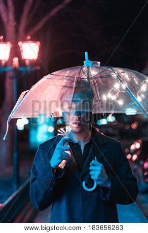 Guy under an umbrella on a night street