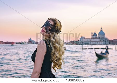 Portrait of a woman with a mysterious look at sunset in Venice. Girl wearing a black mask at Grand Canal, Italy