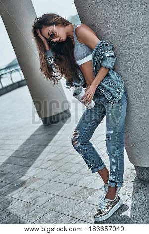 Carefree beauty. Full Length of attractive young woman in jeans wear holding a disposable cup and keeping hand in hair while leaning on the architectural column outdoors