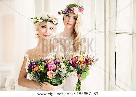 Two Perfect Bride. Blonde Women with Flower Arrangement Flower Wreath Wedding Hairstyle and Makeup