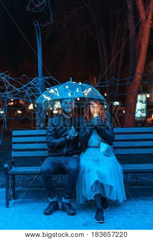 Guy and girl sitting on a bench under an umbrella on a night street