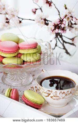 A french sweet delicacy macaroons variety . macaroon and cup of coffee on vintage table for cozy breakfast.