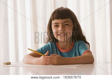 Hispanic girl with paper and pencil