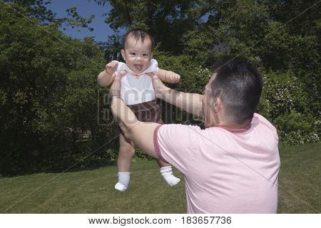 Chinese father lifting baby in park