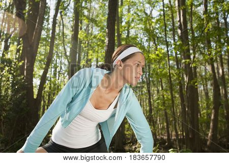 Hispanic woman stretching in forest