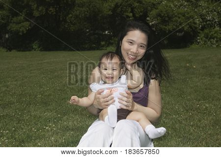 Chinese mother holding baby in park