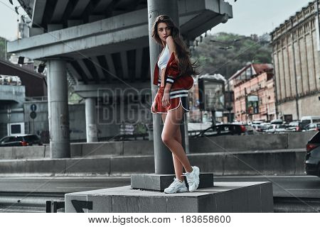 City style. Full length of beautiful young woman in sport clothing looking over shoulder while posing under the bridge outdoors