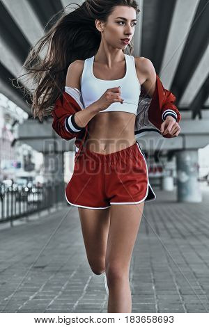 Fresh air jog. Beautiful young woman in sport clothing looking away while running under the bridge outdoors