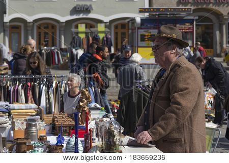 LINZ, AUSTRIA - MARCH 25, 2017:  Old Austrian man selling old vintage forniture in the Hauptplatz Fleamarket in Linz, Austria