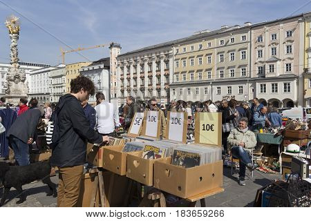 LINZ, AUSTRIA - MARCH 25, 2017:  Young boy looking for old vintage vinyl music in the Hauptplatz Fleamarket in Linz, Austria
