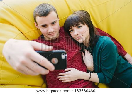 Two smiling young students make beautiful selfie. Portrait of young people in a room on a chair bag