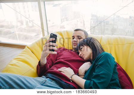 Young beautiful man and girl resting in a room with a modern interior and using a mobile phone. Bag chair in a modern apartment.