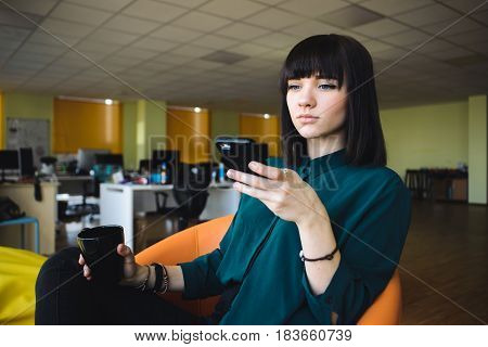 Portrait of smiling modern business woman in office using her mobile phone.Young handsome office worker in a modern office in background jobs. Business woman holding a cup of coffee. Break work.