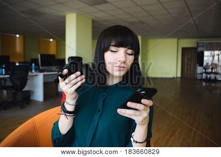 Portrait of a young beautiful woman office worker who uses a mobile phone and holding a cup of drink. Break work. Modern office