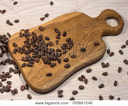 Pine nuts scattered on the table and on a wooden cutting Board. Nuts are chaotic.