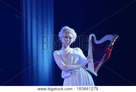 Blonde in a white face, wearing a white dress, holding a harp