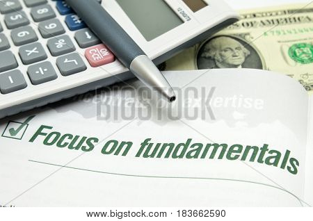 Focus on fundamentals printed on book with calculator and pen.