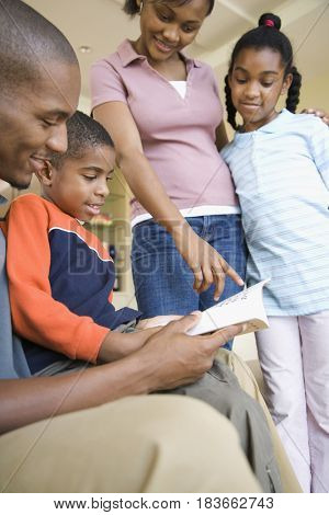 African family looking at book