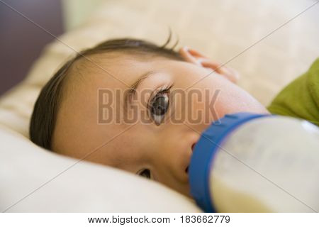 Hispanic baby boy drinking bottle