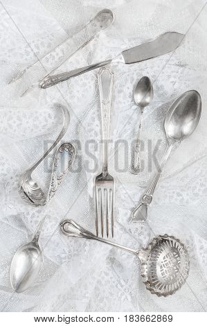 Silverware on a white guipure fabric closeup