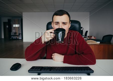 Portrait of a tired young office worker drinking coffee. Against the background of office