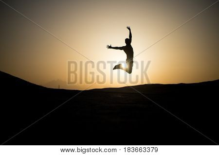 Jumping Man Silhouette At Sunset Sky