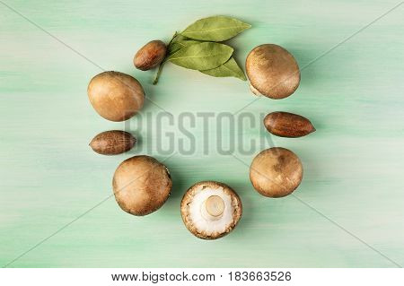 An overhead photo of portobello mushrooms with pecan nuts, and bay leaves, forming a circular frame for text on a teal wooden texture
