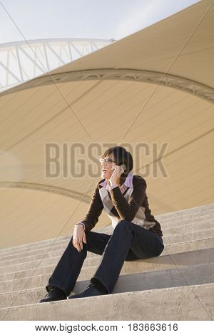 Hispanic woman talking on cell phone on steps