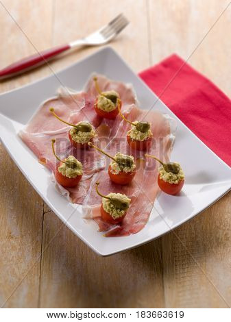 parma ham with stuffed tomatoes, traditional italian appetizer, selective focus