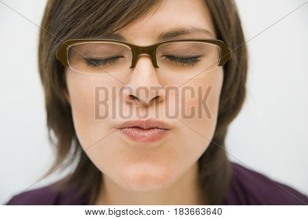 Hispanic woman in eyeglasses puckering for kiss