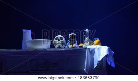The human skull lies on the table with a bottle of wine, grapes and a soft toy. still life