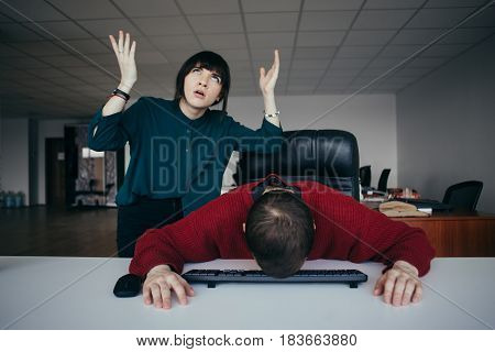 Young Business Woman shouting to his colleague and active gestures the man lowered his head in disappointment keyboard. The situation in the office