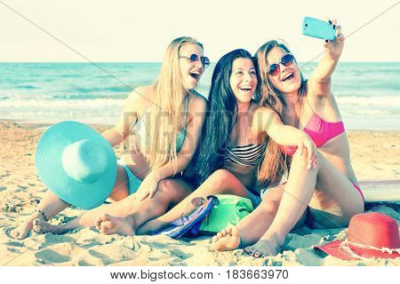 Happy young women taking selfie sitting on the beach at sunset - Beautiful girls having fun moments on summer vacation using mobile phone camera and shouting joyful together