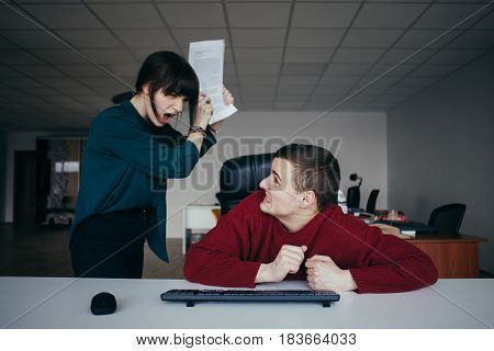 Young and very evil business woman yelling at her colleague and wants to hit its securities. The situation in the modern office.