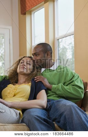 African couple relaxing in living room